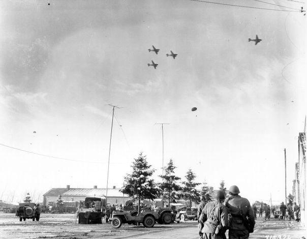 Troops of the 101st Airborne Division watch C-47s drop supplies on Boxing Day 1944
