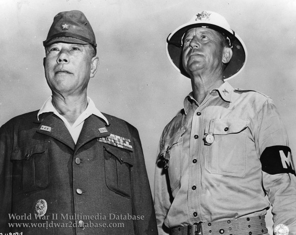 """Lieutenant General Tomoyuki Yamashita, the """"Tiger of Malaya,"""" is arraigned before the War Crimes Commission in Manila, pleading not guilty. He will be confined at New Bilibid Prison until his trial, October 29, 1945, in Manila. Here, Major A. S. """"Jack"""" Kenworthy, Military Police prison officer, delivers Gen. Yamashita to the residence of the Philippine High Commissioner, where Yamashita was held for arraignment in the first step of the war-crime trials to be held in the Pacific. The arraignment was open to the public. Yamashita was brought from his cell in New Bilibid Prison in an ambulance for security reasons. The legitimacy of the hasty trial has been called into question by many, as considerable evidence pointed to the fact that Yamashita was either not aware of the atrocities that were committed, or was unable to properly control his soldiers due to communication disruption caused by the U.S. Army during their offensive. One of the atrocities in Manila was even carried out by a unit that disobeyed his orders to retreat. Following the Supreme Court decision, an appeal for clemency was made to President Truman. The President, however, declined to act and thereby left the matter entirely in the hands of the military. In due time, General MacArthur announced that he had confirmed the sentence of the Commission and on February 23, 1946, at Los Banos Prison Camp, 30 miles south of Manila, Tomoyuki Yamashita was hanged."""